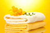 Colorful towels and flowers on yellow background — Stock Photo