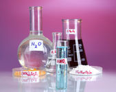 Test-tubes with various acids and chemicals on violet background — Stock Photo