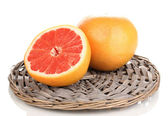 Half of ripe grapefruit on wicker mat isolated on white — Stock Photo