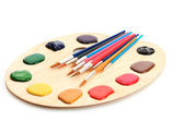 Wooden art palette with paint and brushes isolated on white — Stock Photo