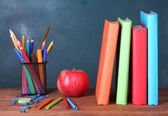 Composition of books, stationery and an apple on the teacher's desk in the background of the blackboard — Foto de Stock