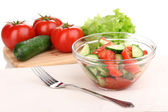 Fresh salad with tomatoes and cucumbers isolated on white — Stock Photo