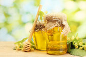 Jars with linden honey and flowers on wooden table on green background — Stock Photo