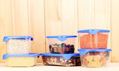 Filled plastic containers on wooden background — 图库照片