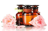Bottles of oil and roses isolated on white — Stock Photo