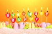 Tort urodzinowy z świece na żółtym tle — Zdjęcie stockowe