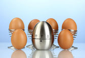 Egg timer and eggs on blue background — 图库照片