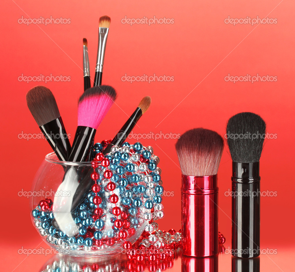 Make-up brushes in a bowl with pearl necklace on red background — Stock Photo #11736151