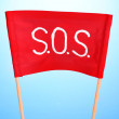 SOS signal written on red cloth on blue background - Stock Photo