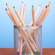 Color pencils in glass on wooden table on blue background — Stock Photo #11759951