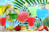 Glasses cocktails on table on blue sea background — Stock Photo