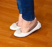 Gambe in jeans e ballerine piatte su fondo in legno — Foto Stock