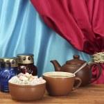 czajnik filiżanka i spodek z słodki Turcy na drewnianym stole na tle kurtyny z bliska — Zdjęcie stockowe
