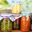 Jars with canned vegetables on green background close-up - Stockfoto