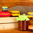 Jars with canned fruit on wooden background - Photo