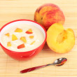 Yoghurt with peach in bowl on bamboo mat — Stock Photo #11760666