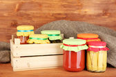 Jars with canned vegetables on wooden background close-up — Stock Photo