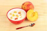 Joghurt mit pfirsich in schüssel auf bambusmatte — Stockfoto