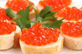 Red caviar on bread on white plate close-up — Stock Photo