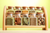 Powder spices in glass jars on wooden shelf on green background — Stock Photo