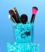 青色の背景に石とカップのメイクブラシ — ストック写真