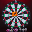 Stock Photo: Darts with sticker symbolizing love on colorful background