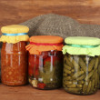 Jars with canned vegetables on wooden background close-up — Stock Photo #11780666