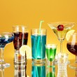 Variety of alcoholic drinks on yellow background — Stock Photo #11787639