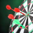 Stock Photo: Dart board with darts on green background