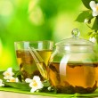 Green tea with jasmine in cup and teapot on wooden table on green background - Foto de Stock