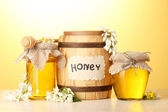 Sweet honey in barrel and jars with acacia flowers on wooden table on yellow background — Stock Photo