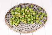 Green gooseberry on wicker mat on wooden background — Stock Photo