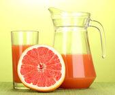 Grapefruit juice and grapefruit on bamboo mat on green background — Stock Photo