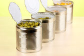 Open tin cans of peas, corn, bean and french bean on wooden table on green background — Stock Photo