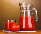 投手と茶色の背景に木製のテーブルの上のガラスのトマト ジュース — ストック写真