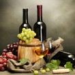 Barrel, bottles and glasses of wine and ripe grapes on wooden table on grey background — Stock Photo