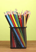 Color pencils in glass on wooden table on green background — Stock Photo