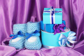 Blue baby boots and gifts on silk background — Stock Photo