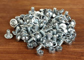 Chrome nuts and bolts on wooden background close-up — Stock Photo