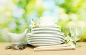 Empty clean plates, glasses and cup on wooden table on green background — Foto Stock