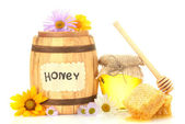 Sweet honey in jar and barrel with honeycomb, wooden drizzler and flowers isolated on white — Stock Photo