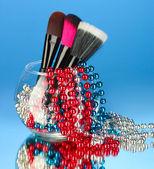 Pędzle do makijażu w misce z perłą naszyjnik na niebieskim tle — Zdjęcie stockowe