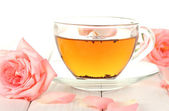 Cup of tea with roses on white wooden table — Stock Photo