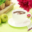 Cup hot chocolate, apples and flowers on table in cafe — ストック写真