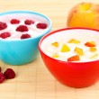 Yogurt with peaches and raspberries in bowls on bamboo mat — Stock Photo