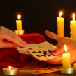 Fortune-telling and woman's hands on black backcground - Stock Photo