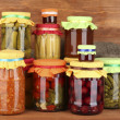 Jars with canned vegetables and fruit on wooden background close-up - Stockfoto