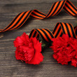 Carnations and St. George's ribbon on grey wooden background - Stock Photo