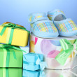 Beautiful gifts and baby's bootees on blue background — Stock Photo #11845498