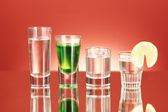 A variety of alcoholic drinks on red background — Stock Photo
